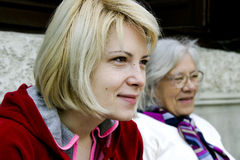 Grandmother and granddaughter. Blond granddaughter sitting next to gray grandmother; both are looking off to the side Royalty Free Stock Photo
