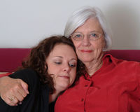 Grandmother, Granddaughter. Grandmother  hugging granddaughter while sitting on couch Royalty Free Stock Images