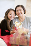 Grandmother And Granddaughter. Exchanging Christmas Gifts Royalty Free Stock Images