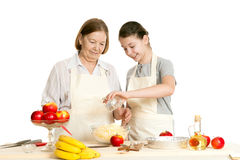 The grandmother and the granddaughter add ingredients Royalty Free Stock Images
