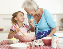 Grandmother And Granddaughter Baking In Kitchen Stock Images