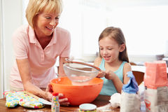 Grandmother And Granddaughter Baking Together At Home Stock Photography