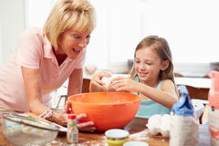 Grandmother And Granddaughter Baking Together At Home Stock Image