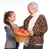 Grandmother with granddaughter with basket of apples Royalty Free Stock Image