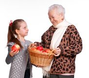 Grandmother with granddaughter with basket of apples Stock Images