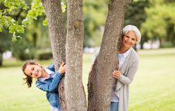 Grandmother and granddaughter behind tree at park. Family, leisure and people concept - happy grandmother and granddaughter peeking out tree at summer park stock image