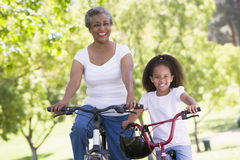 Grandmother and granddaughter on bikes outdoors. Smiling Stock Image