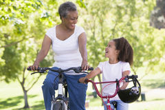 Grandmother and granddaughter on bikes outdoors stock images