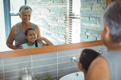 Grandmother and granddaughter brushing teeth in the bathroom stock images
