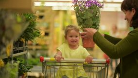 Grandmother and Granddaughter Are Buying Smelling Flowers at the Shopping Mall. A Flower Pot is Brown, But Flowers Are. Purple. HD, Family, Shopping stock video footage