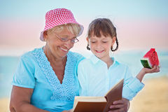 Grandmother with granddaughter. Child and grandmother eating watermelon on the beach Stock Image