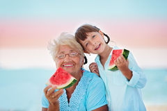 Grandmother with granddaughter. Child and grandmother eating watermelon on the beach Royalty Free Stock Photography