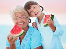 Grandmother with granddaughter. Child and grandmother eating watermelon on the beach Royalty Free Stock Photos