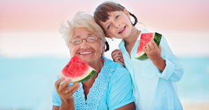 Grandmother with granddaughter. Child and grandmother eating watermelon on the beach Stock Photography