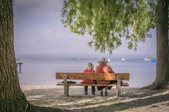 Beautiful family on the bench at the beach royalty free stock image