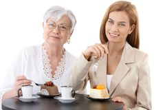 Grandmother and granddaughter at coffee shop. Grandmother and granddaughter sitting at table at coffee shop, eating cake, drinking coffee, smiling Stock Photography