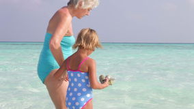 Grandmother And Granddaughter Collecting Rocks On Beautiful Beach Stock Image