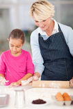 Grandmother granddaughter cookies. Cute grandmother and granddaughter making cookies in kitchen Royalty Free Stock Image