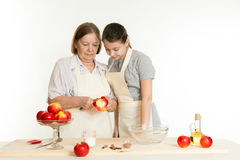 The grandmother and the granddaughter cut off a peel from apple Stock Photography