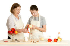 The grandmother and the granddaughter cut off a peel from apple Royalty Free Stock Image