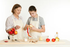 The grandmother and the granddaughter cut off a peel from apple Stock Image