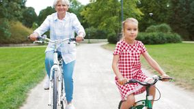 Grandmother and granddaughter cycling at park stock video footage