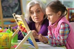 Grandmother and granddaughter do homework Stock Photos
