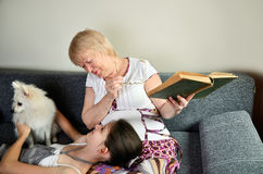 Grandmother and granddaughter with the dog laughing sit on the c. Ouch and looking at each other horizontal Stock Photo
