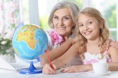 Grandmother and granddaughter doing homework Stock Image