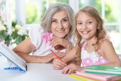 Grandmother and granddaughter doing homework. At home together Stock Photo