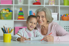 Grandmother with granddaughter drawing together Royalty Free Stock Images