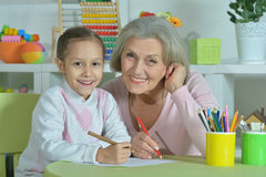 Grandmother with granddaughter drawing together Royalty Free Stock Photos