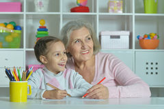 Grandmother with granddaughter drawing together Stock Image