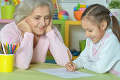 Grandmother with granddaughter drawing together Stock Images