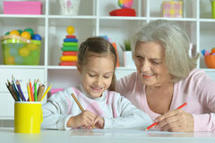 Grandmother with granddaughter drawing together Stock Photos