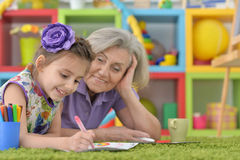 Grandmother with granddaughter drawing together Royalty Free Stock Photography