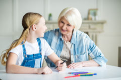 Grandmother and granddaughter drawing together and smiling each other Stock Photos