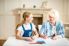 Grandmother and granddaughter drawing together and smiling each other Stock Images