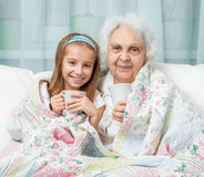 Grandmother and granddaughter drink tea. Covered with blanket Stock Photography