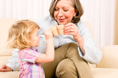 Grandmother with granddaughter drink tiny cups Stock Photos
