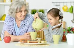 Grandmother and granddaughter drinking tea. At kitchen Royalty Free Stock Image