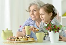Grandmother and granddaughter drinking tea. At kitchen Stock Photos