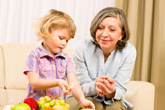 Grandmother with granddaughter eat fruit at home Stock Photo