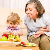 Grandmother with granddaughter eat fruit at home Royalty Free Stock Images