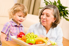 Grandmother with granddaughter eat fruit at home Stock Images