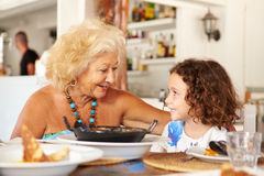 Grandmother And Granddaughter Enjoying Meal In Restaurant Royalty Free Stock Images