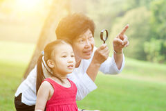 Grandmother and granddaughter exploring outdoor. Royalty Free Stock Photos