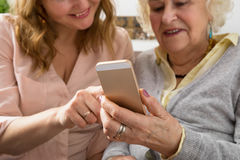 Grandmother and granddaughter exploring smartphone. Grandmother and granddaughter exploring new smartphone Stock Photography