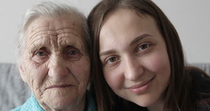 Grandmother and granddaughter faces looking together at camera. stock video footage