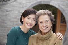 Grandmother and granddaughter in front of round arch, Beijing Royalty Free Stock Photo
